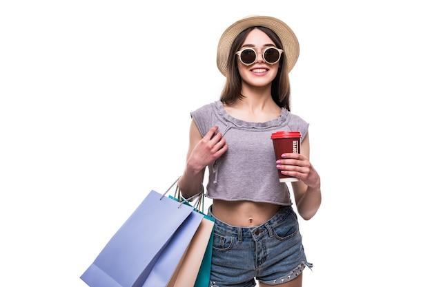 Mooie vrouw met boodschappentassen en koffiedocument mok geïsoleerd te houden Gratis Foto