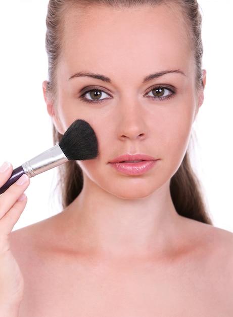 Mooie vrouw met borstel voor make-up Gratis Foto