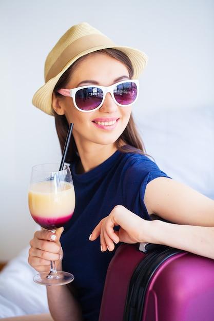 Mooie vrouw met cocktail en koffer op bed in hootelruimte Premium Foto