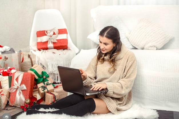 Mooie vrouw met computer en kerstmisgiften. Gratis Foto