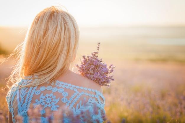 Mooie vrouw met een boeket van lavendel die van de zonsondergang geniet Premium Foto