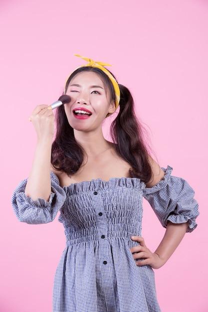 Mooie vrouw met een borstel, geborsteld op een roze achtergrond. Gratis Foto