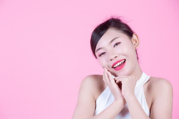 Mooie vrouw met een gezonde huid en schoonheid op een roze achtergrond. Gratis Foto