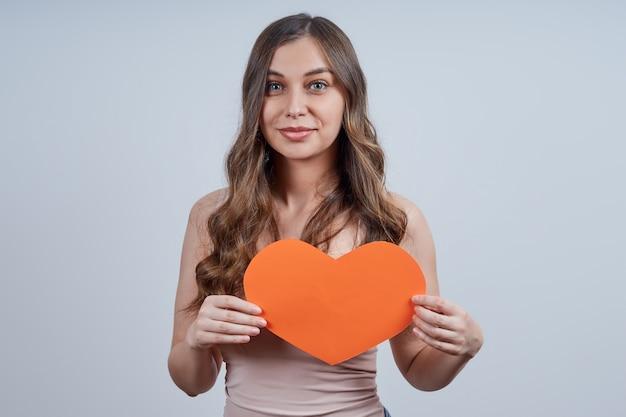 Mooie vrouw met een hart van papier op haar borst, kijkend naar de camera, op een grijze achtergrond. fijne valentijnsdag. wereldhartdag. Premium Foto
