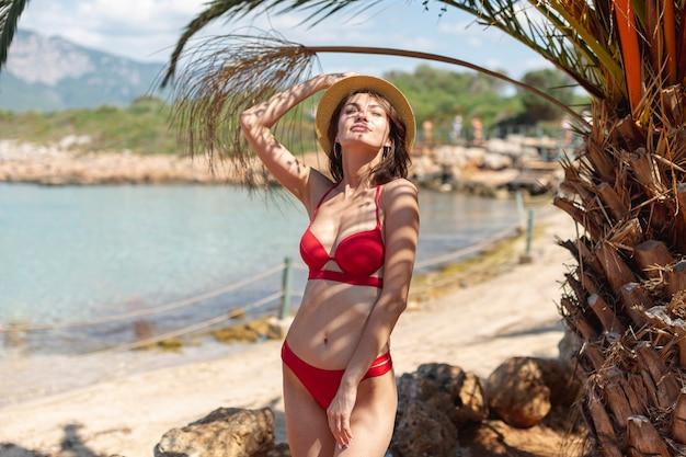 Mooie vrouw met een hoed in de buurt van een palmboom Gratis Foto