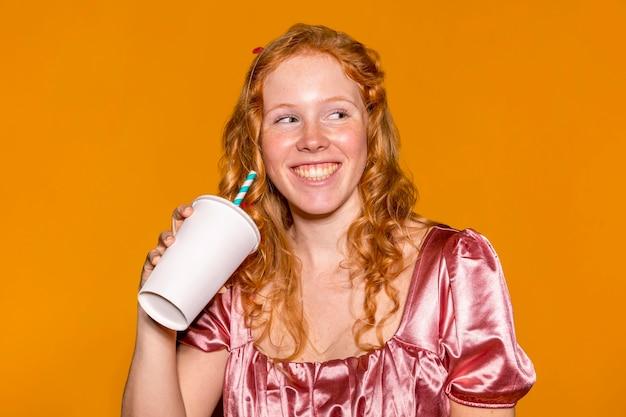Mooie vrouw met een kartonnen beker Premium Foto