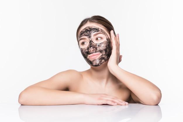 Mooie vrouw met een klei of een moddermasker op haar gezicht dat over witte muur wordt geïsoleerd Gratis Foto