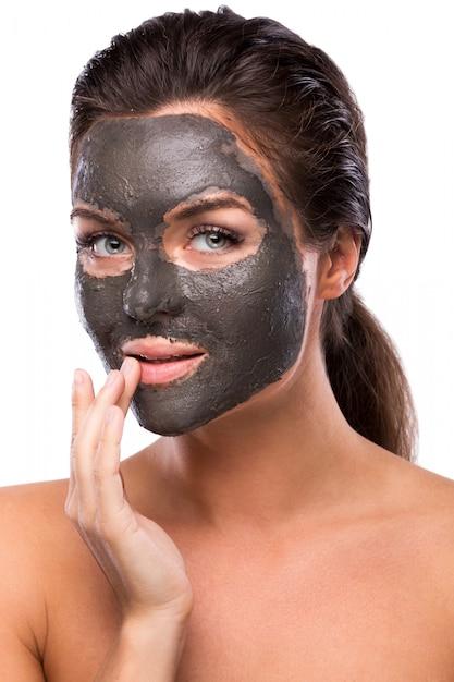 Mooie vrouw met een klei of een moddermasker op haar gezicht Premium Foto