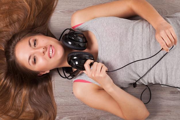 Mooie vrouw met een koptelefoon op de vloer liggen Gratis Foto