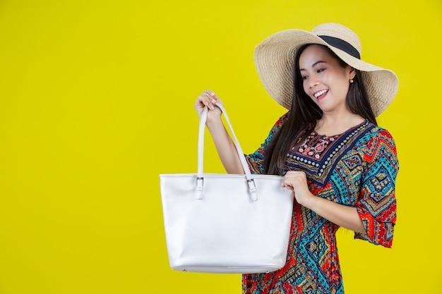 Mooie vrouw met een zak in het geel Gratis Foto
