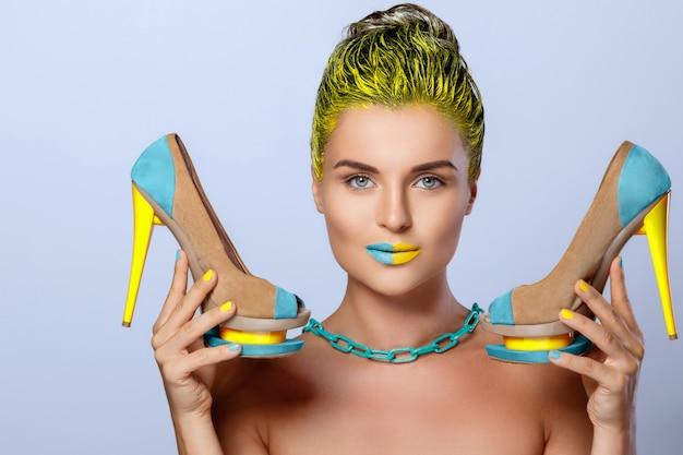 Mooie vrouw met gele holdings kleurrijke schoenen Premium Foto