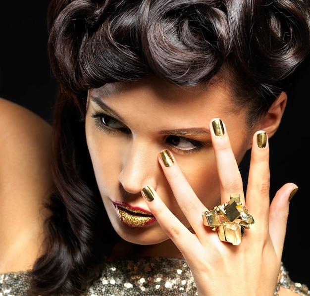 Mooie vrouw met gouden spijkers en maniermake-up van ogen. brunet meisjesmodel met stijlmanicure op zwarte muur Gratis Foto