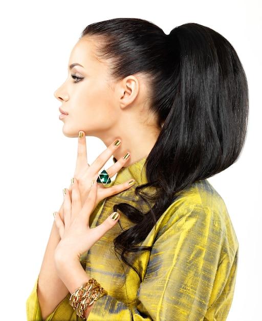 Mooie vrouw met gouden spijkers en mooie edelsteensmaragd Gratis Foto
