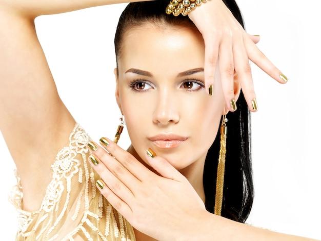 Mooie vrouw met gouden spijkers en mooie gouden die juwelen op wit worden geïsoleerd Gratis Foto