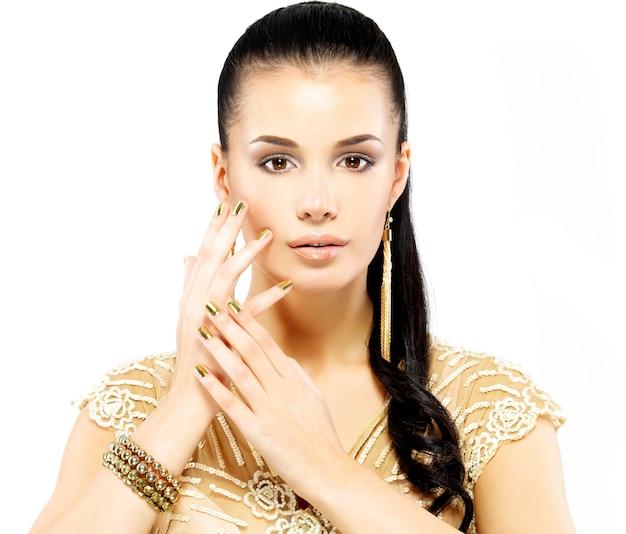 Mooie vrouw met gouden spijkers en mooie gouden juwelen die op witte achtergrond worden geïsoleerd Gratis Foto