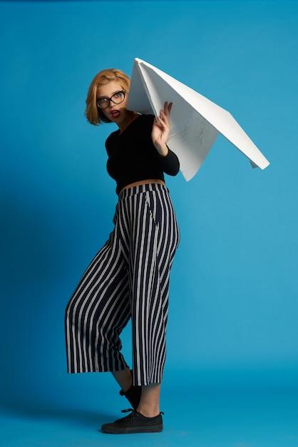 Mooie vrouw met groot papieren vliegtuigje Premium Foto
