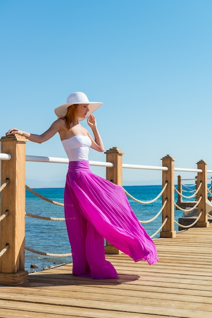 Mooie vrouw met hoed en roze rok Gratis Foto