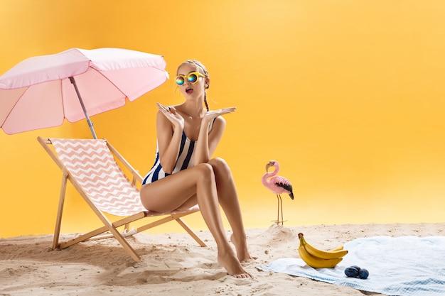 Mooie vrouw met kleurrijke zonnebril kijkt verrast op lichte achtergrond Gratis Foto
