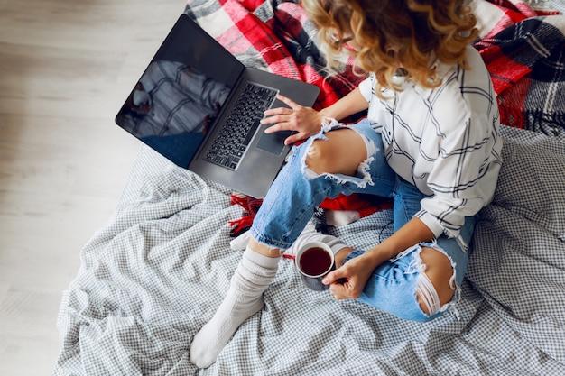 Mooie vrouw met kop koffie en laptop Gratis Foto