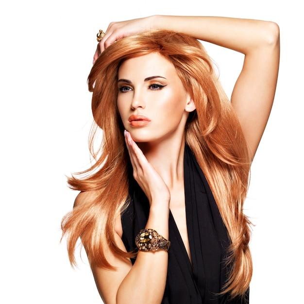Mooie vrouw met lang recht rood haar in een zwarte jurk aan haar gezicht te raken. mannequin poseren. geïsoleerd op wit Gratis Foto