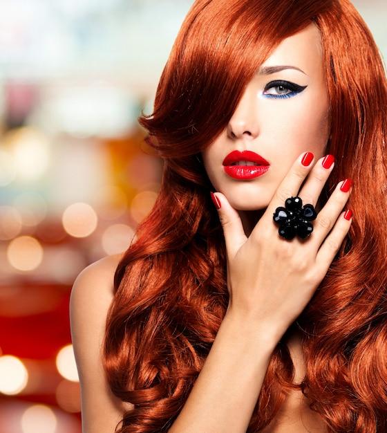 Mooie vrouw met lange rode haren met sexy heldere lippen en rode nagels. Gratis Foto