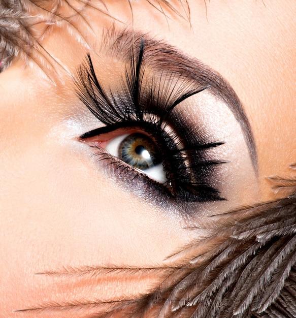 Mooie vrouw met lichte professionele make-up met veren in de buurt van het gezicht. Gratis Foto