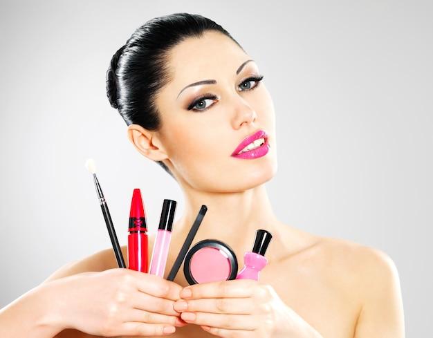 Mooie vrouw met make-up cosmetische hulpmiddelen in de buurt van haar gezicht. Gratis Foto