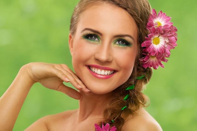 Mooie vrouw met make-up en bloemen Gratis Foto