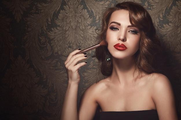 Mooie vrouw met make-upborstel Premium Foto