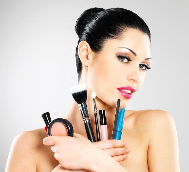 Mooie vrouw met make-upborstels dichtbij haar gezicht. Gratis Foto