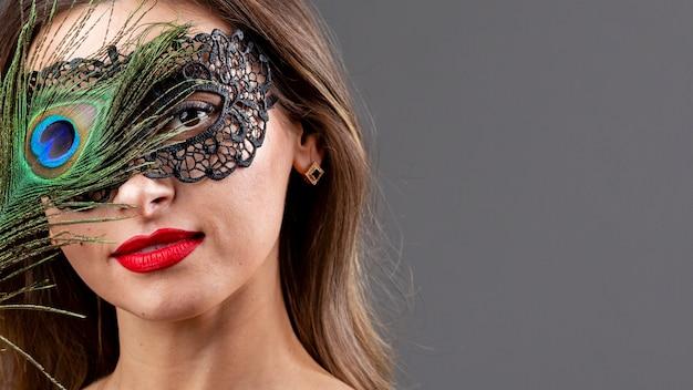 Mooie vrouw met masker en pauwenveer Gratis Foto