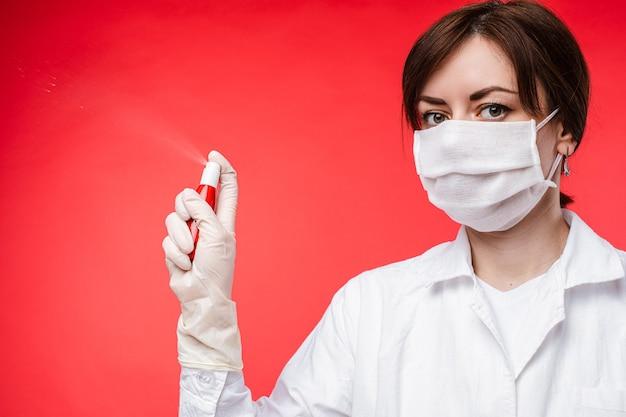 Mooie vrouw met medisch masker verspreidt antiseptisch in de lucht, foto geïsoleerd op rode achtergrond Gratis Foto