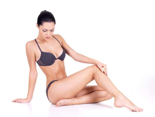 Mooie vrouw met perfect slank lichaam zit op witte achtergrond Gratis Foto