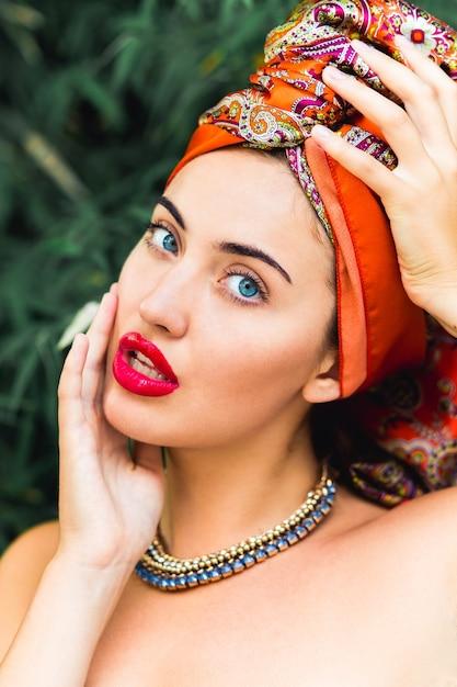 Mooie vrouw met perfecte make-up en oranje hoofddoek, rode grote lippen, blauwe ogen, handen op het hoofd Gratis Foto
