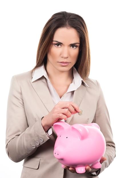 Mooie vrouw met spaarvarken en muntstuk Gratis Foto