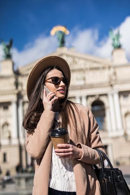 Mooie vrouw met steunen in zonnebril die in vrijetijdskleding in de stad stellen Gratis Foto