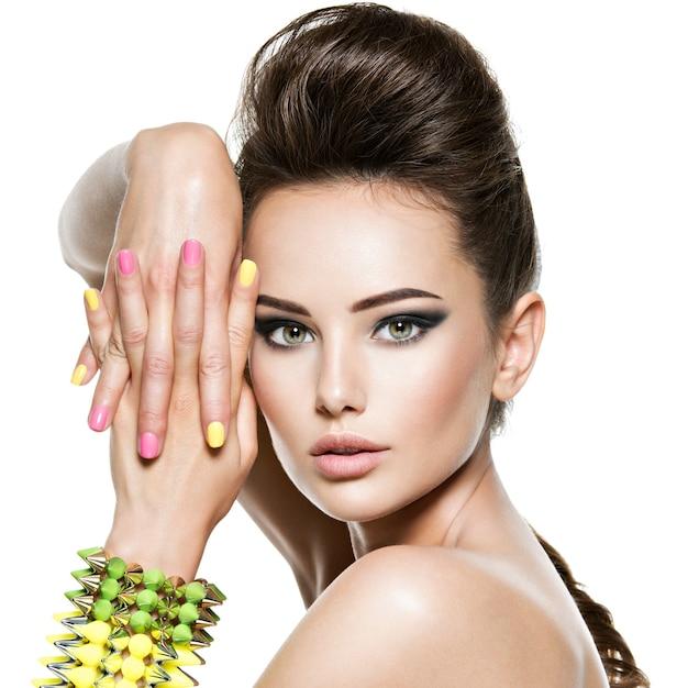 Mooie vrouw met veelkleurige nagels en bezaaid armband bij de hand Gratis Foto
