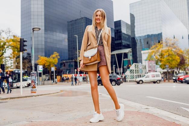 Mooie vrouw met verrassingsgezicht die langs de straat loopt. beige jas en sneakers dragen. new york. perfecte lange benen. elegante uitstraling. Gratis Foto