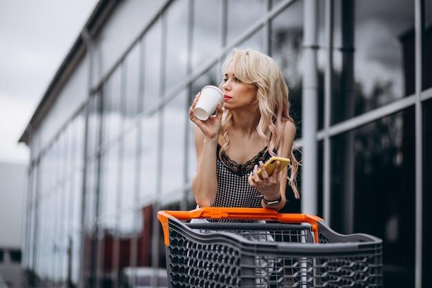 Mooie vrouw met winkelwagen buiten Gratis Foto