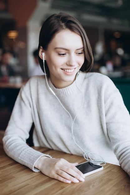 Mooie vrouw natuurlijke gezicht close-up casual vrouwelijke portret levensstijl schoonheid meisje met smartphone in café Premium Foto