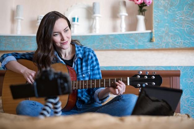 Mooie vrouw op bed in de slaapkamer, neemt muziekblog op en speelt akoestische gitaar Premium Foto