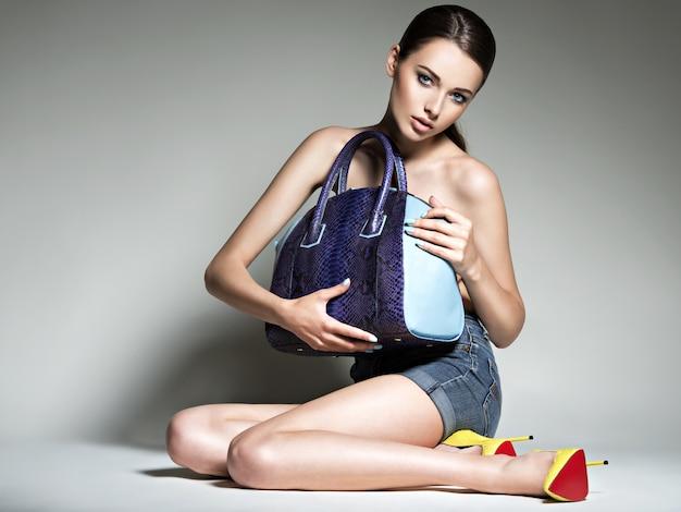 Mooie vrouw op hoge hakken houdt handtas. mode jong meisje met lange benen, naakte lichaam poseren in studio Gratis Foto