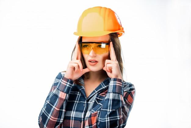 Mooie vrouw oranje beschermende helm dragen en glazen die hoofdpijn hebben en vingers op hoofd houden dat op wit wordt geïsoleerd Premium Foto