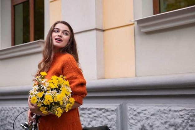 Mooie vrouw poseren buitenshuis met boeket bloemen en fiets Premium Foto