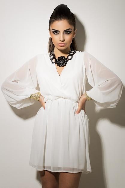 Mooie vrouw poseren in witte jurk Gratis Foto
