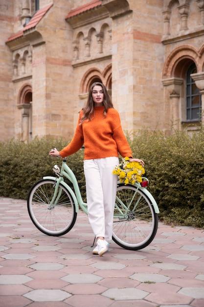 Mooie vrouw poseren met fiets en bloemen buitenshuis Gratis Foto