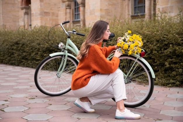 Mooie vrouw poseren naast fiets met bloemen buitenshuis Gratis Foto