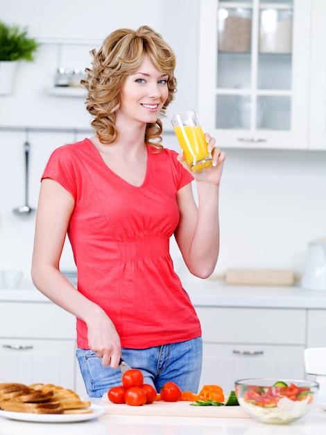 Mooie vrouw sinaasappelsap drinken en koken in de keuken - binnenshuis Gratis Foto