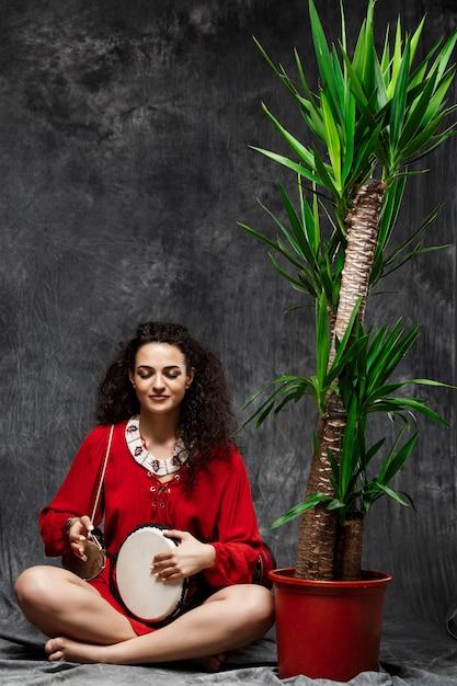Mooie vrouw speeltrommel in tropische planten over grijze muur Gratis Foto