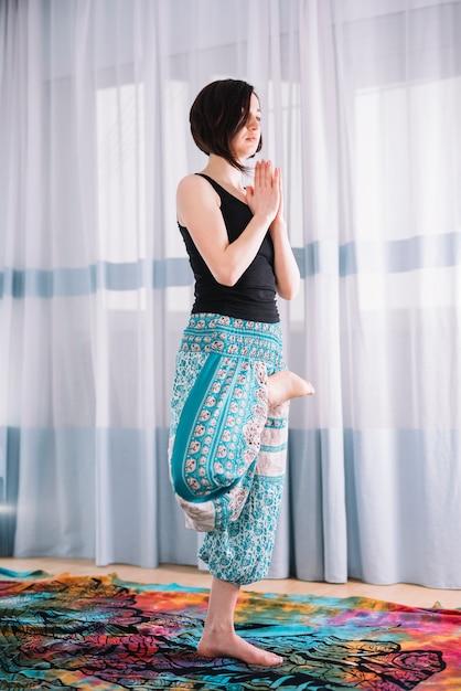 Mooie vrouw thuis het beoefenen van yoga en meditatie Gratis Foto